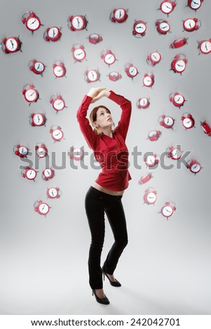 standing woman with arms up above her head protecting  her self from falling clocks
