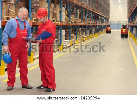 standing workers in warehouse reading invoice - stock photo