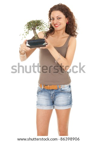 standing young casual woman with bonsai tree - stock photo