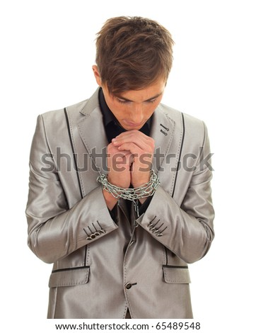 standing young man in grey suit with chained hands - stock photo