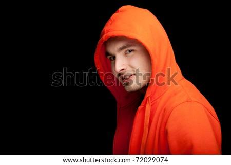 standing young man in orange sweatshirt and hood , black background - stock photo