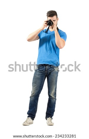 Standing young man taking photo with dslr looking at camera. Full body length portrait isolated over white background. - stock photo