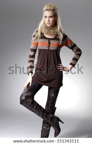 standing young woman in boots posing over white background - stock photo