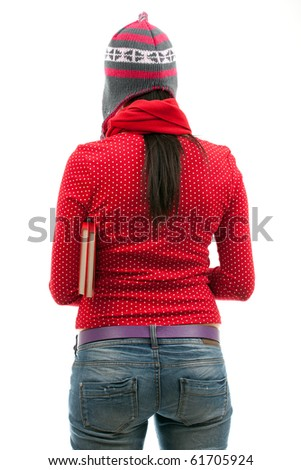 standing young woman in woollen hat holding book - stock photo