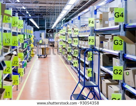 stands with carton boxes in storage warehouse - stock photo