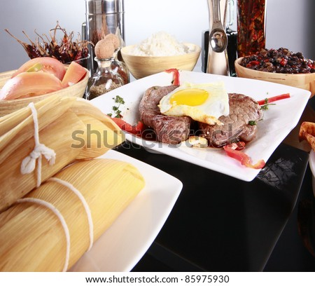 Staple latino meal; steak; egg; tamale; rice; and black beans - stock photo