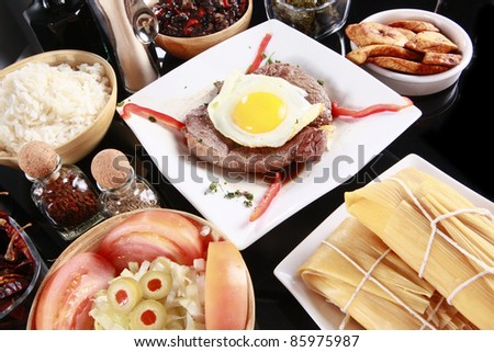 Staple latino meal, steak; egg; tamale; rice; and black beans - stock photo