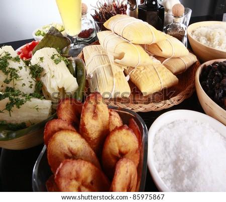 Staple latino sides, manioc, rice, plantains, tamale, and black beans - stock photo