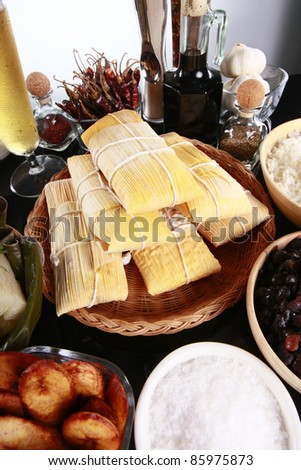 Staple latino sides, tamale, rice, plantains, and black beans - stock photo