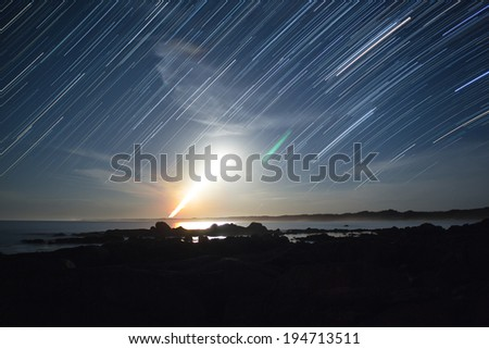 star and moon trails, the moon looks like a rocket, or explosion - stock photo
