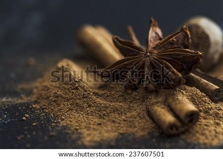 Star anise, cinnamon and nutmeg on black background - stock photo