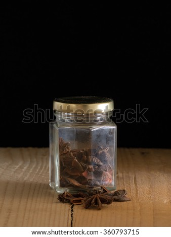 Star anise inside a jar with dark background and wooden platform