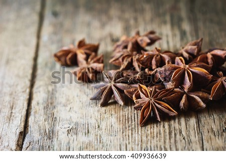 Star anise spice and fruit seeds on vintage wooden background. Close-up. Selective focus - stock photo
