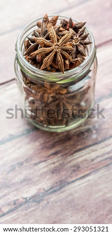 Star anise spice in a mason jar over weathered background