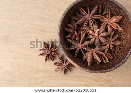 Star Anise spice in a wooden bowl from above.