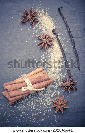 Star anise with cinnamon sticks over black stones background at christmas time