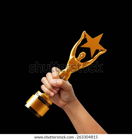 Star award in hand on black background. - stock photo