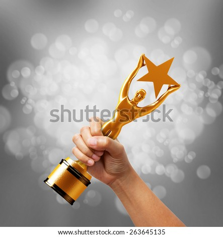 Star award in hand on silver background. - stock photo