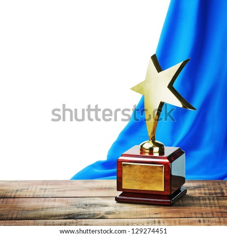 Star award wooden table and on the background of blue curtain with space for text - stock photo