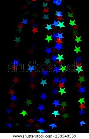 Star bokeh lights on black background - stock photo