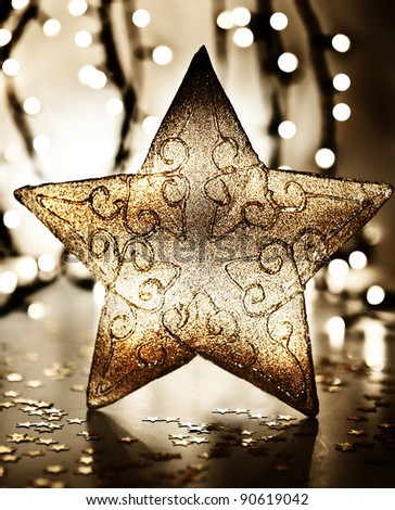 Star, Christmas tree ornament, golden decoration over blur lights, dark new Year eve background, winter holidays home decor - stock photo