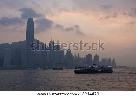 Star ferry crossing vistoria harbour, Hong Kong at sunset - stock photo