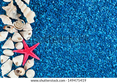 Star-fish and seashells on blue sand - stock photo