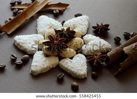 Star made of white coconut heart shaped biscuits with chocolate almond candies and anise spices, cinnamon sticks and coffee beans still life, holiday food background
