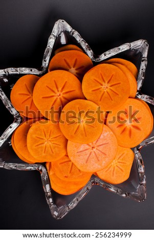 Star platter with sliced persimmons close-up on black background - stock photo