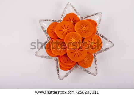 Star platter with sliced persimmons - top view - stock photo