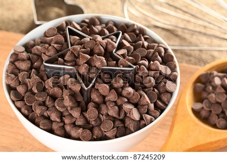 Star-shaped cookie cutter with chocolate chips in a bowl surrounded by baking utensils (Selective Focus, Focus on the front of the cutter and the chocolate chips around) - stock photo