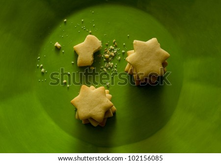Star shaped cookies on vibrant green plate - stock photo