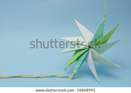 star shaped paper origami tied by a thread at ends with selective focus