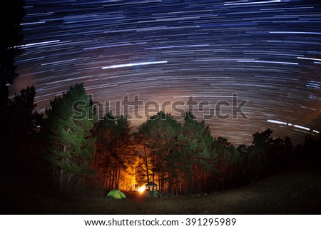 Star tracks over the forest and tourist camp - stock photo