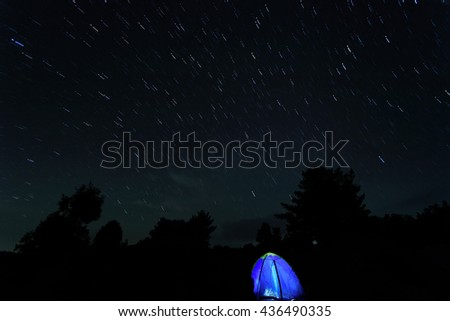 Star trail against tent. Beautiful night sky.  - stock photo