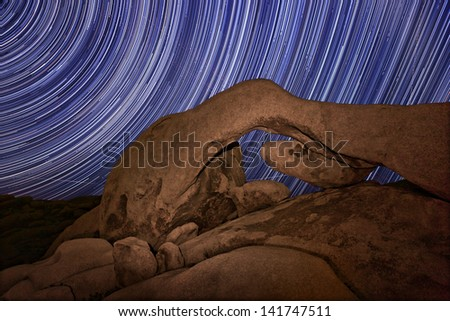 Star Trail Streaks over the Rocks of Joshua Tree Park - stock photo