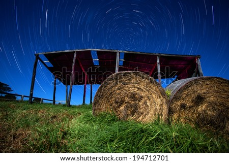 star trails above a hay shed - stock photo