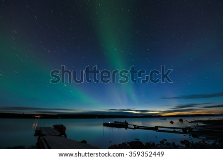 Star Trails and Aurora - Long exposure to capture star trails and light aurora borealis over a lake after the sunset.  - stock photo