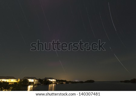 Star Trails at night over the ocean and a cabin by the sea - stock photo