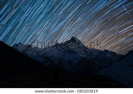Star trails over Mt. Machapuchare, Annapurna Range, Nepal. - stock photo