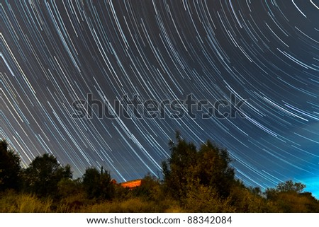 Star trails over over a country house