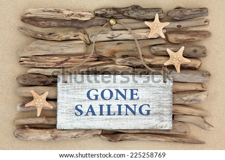 Starfish and gone sailing old weathered sign on driftwood and beach sand background. - stock photo