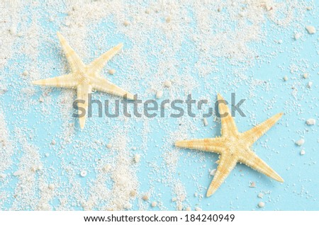 Starfish and sand on blue background