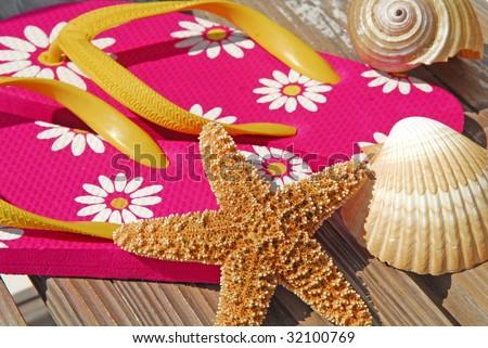 starfish and seashells by flipflops on beach boardwalk - stock photo