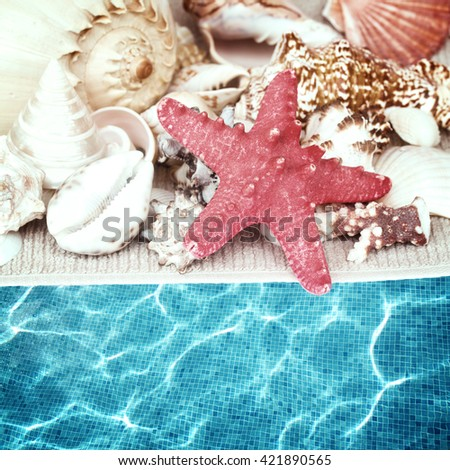 starfish and seashells on towel by pool water, retro toned - stock photo