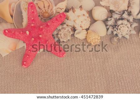 starfish ans seashells on towel with copy space, retro toned - stock photo