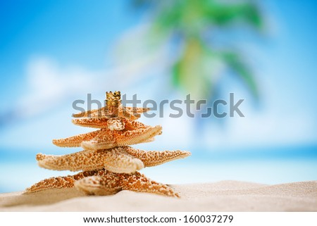 starfish christmas tree on beach with seascape background - stock photo