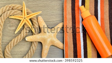 Starfish, color towel and sunscreen spray against on wooden background.