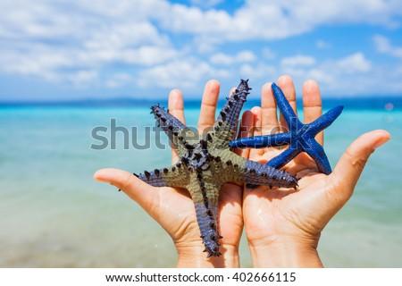 Starfish in girl hands - stock photo