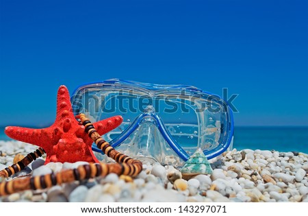 starfish, necklace and diving mask on white pebbles by the shore - stock photo